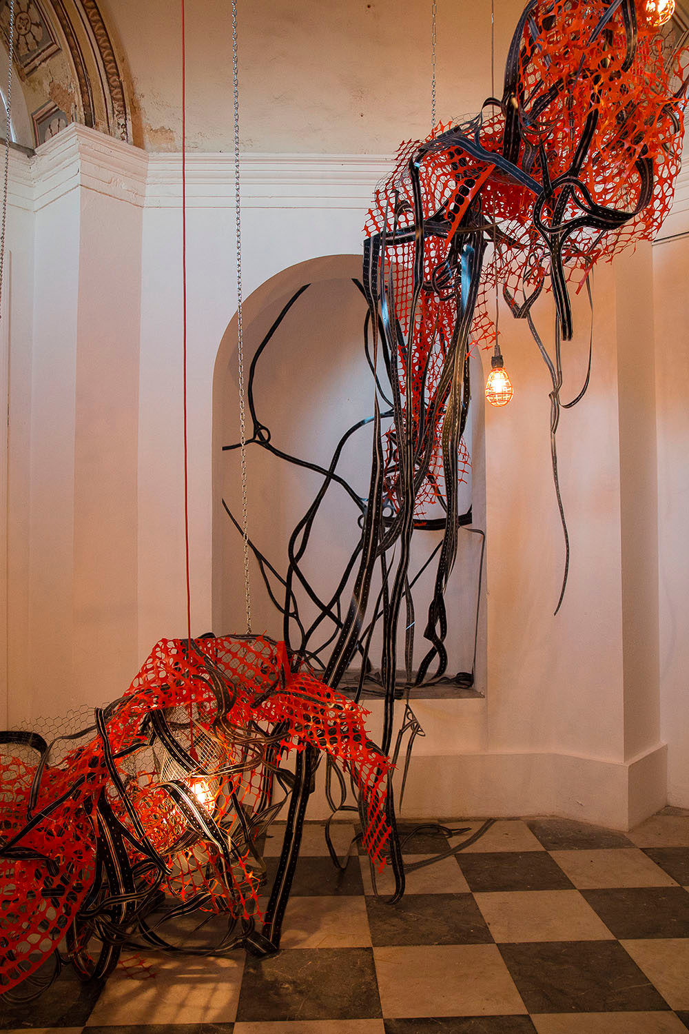 """Closed System III  (installation view) 2015; Woodcut on mylar, fencing, extension cords, tape chains, lights and zip ties; 30' x 22' x 22"""" Shown here at  4ta: Trienal Poli/Gráfica de San Juan: América Latina y el Caribe , San Juan, Puerto Rico"""