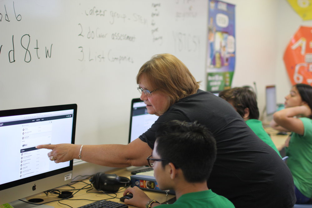 Ewa Makai teacher pointing to a computer screen to assist a student with assignment in class.