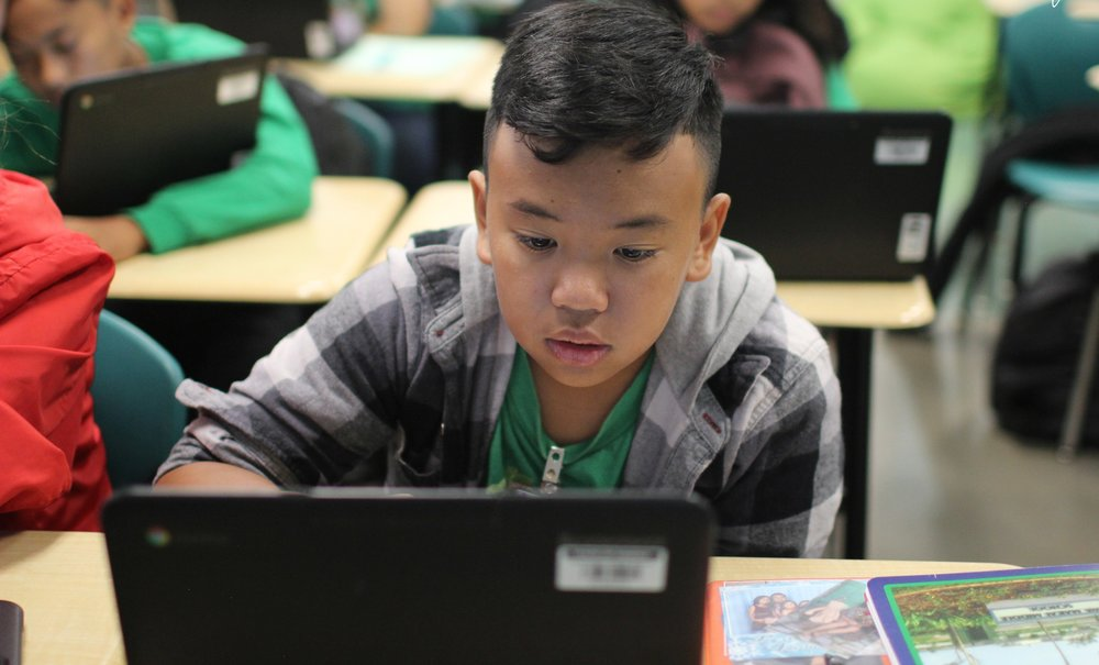 An Ewa Makai student on a computer in class focused on his work.