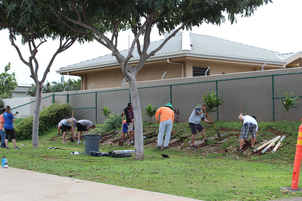 A group of volunteers using shovels to dig out a design on the landscape at the front of Ewa Makai Middle School.