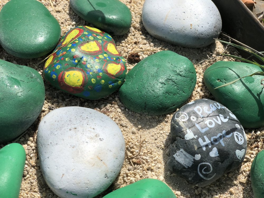 "Decorated painted stones that are part of the landscape design with one saying ""Peace, Love, Hope""."