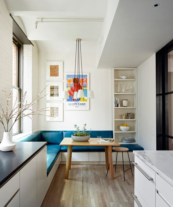 Don't you just want to have your coffee every morning right here? Designed by  Lang Architecture , this sunny kitchen nook really comes together with the blue bench cushion, shelving detail on the side, the colorful art on the wall and the natural wood accent furniture.