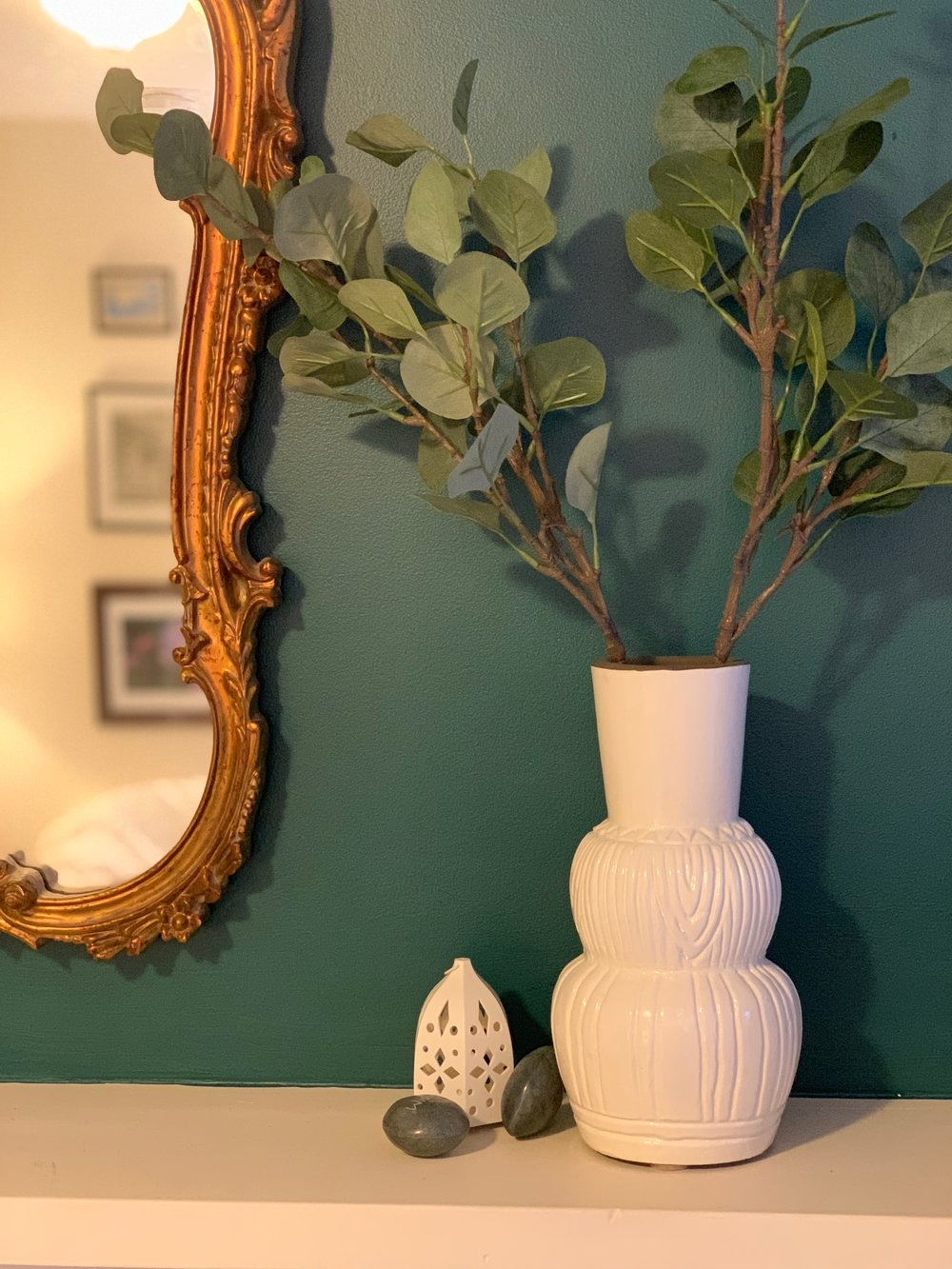 White terra cotta opalhouse vases, ikea lanterns and a vintage gold mirror on a benjamin moore deep teal wall