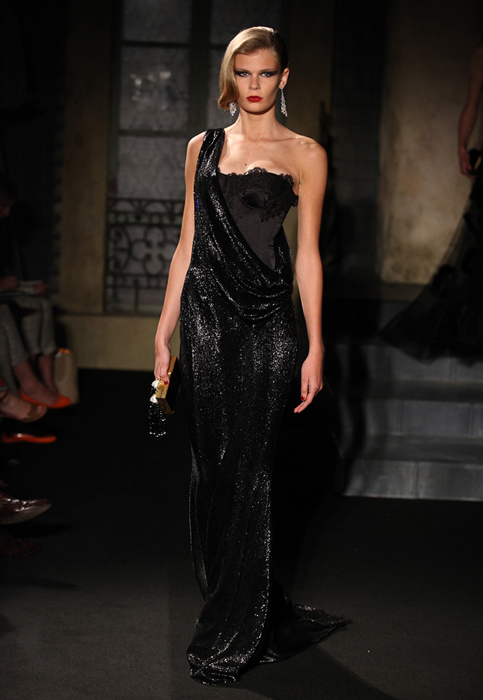 Black beaded gown with exposed corset with black snakeskin & gold tassel bag and black satin shoes