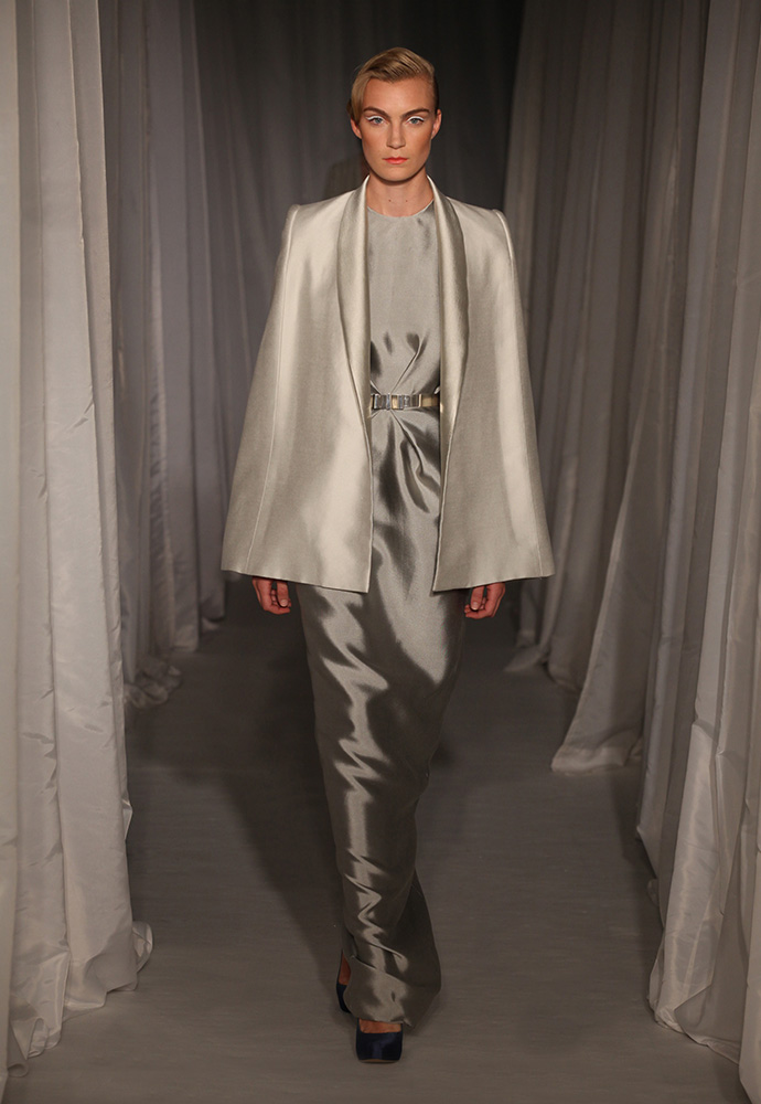 Silver tuck column gown and white tuxedo cape both in silk with slim silver bow belt