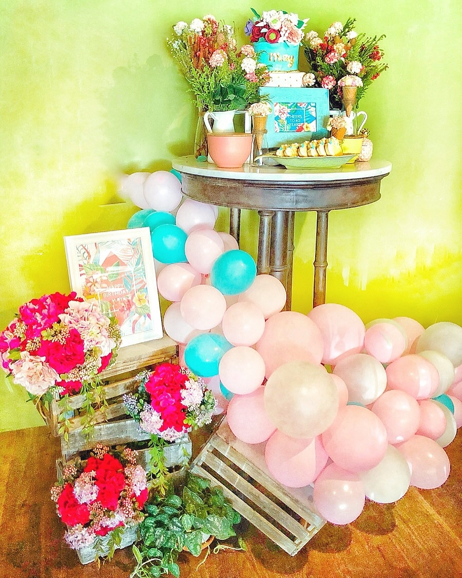 Vintage Caribbean Celebration - Guests had to enter via this rustic wooden staircase and they were met by a custom designed signage with potted plants. The long table was lined with floral lanterns on top. The tables were small so we made mini floral arrangements with gold toppers. Each place setting had a custom made menu card and cookie favor.We had a mini birthday cake table which we flanked with a stack of styled crates with florals and a balloon garland. The tropical cake had beautiful fondant flowers and it was surrounded with lush floral arrangements, floral icing cones and custom made cookies.The other side of the room had a huge rectangular table where we put the main centerpiece with acrylic painted frames, cookies, crates and plants, all of which matched the interiors perfectly.