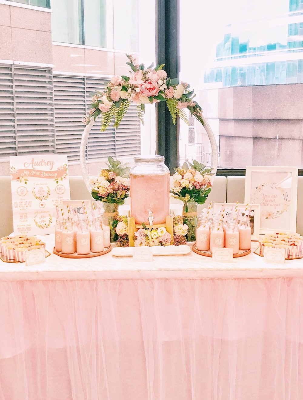 - Our drinks and fruit table was equally amazing with this amazing floral wreath and accents. We had monogrammed bottles with strawberry milk, a large pink lemonade tap surrounded by florals, and monogrammed fruit cups for the little ones. We displayed a framed print and Audrey's milestone board as well.