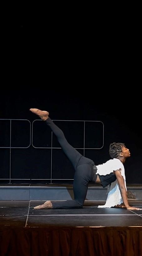 Scynthia balancing on one knee with downstage leg extended up and palms on floor with looking in front of her.