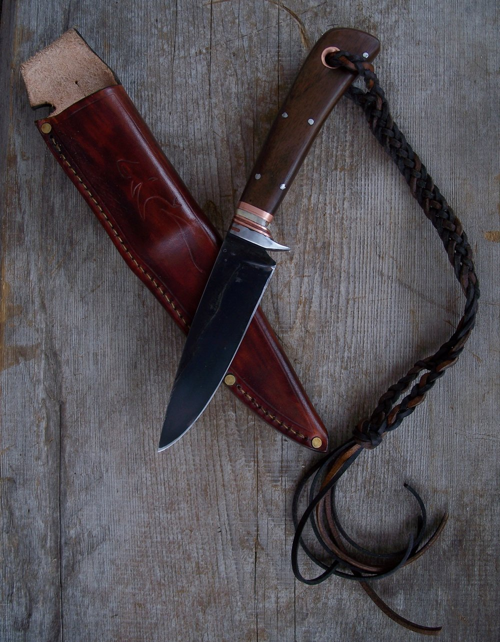 Hand forged drop point hunting knife. Custom long locking lanyard. Visit our  custom sheaths .