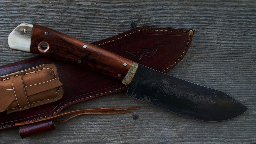 Handmade custom bush craft knife with cherry wood heart scales, Moose antler butt and bolster. Brass pins and a copper lanyard hole insert.