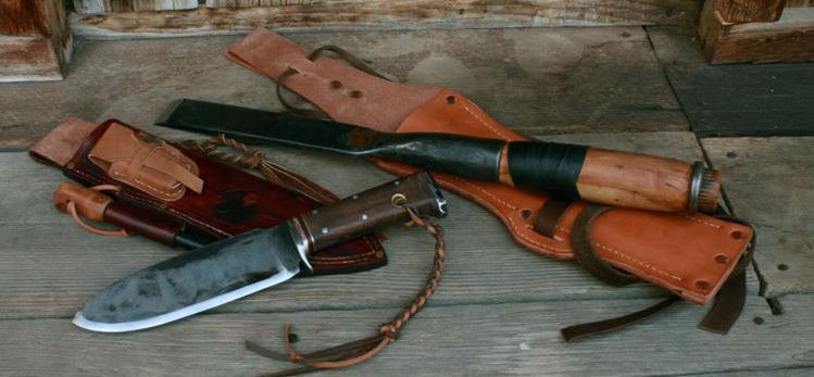Hand forged bushcraft tools and knives laying on their custom made sheaths. A loaded handmade survival bushcraft sheath and a timber framing belt sheath with a leg tie.