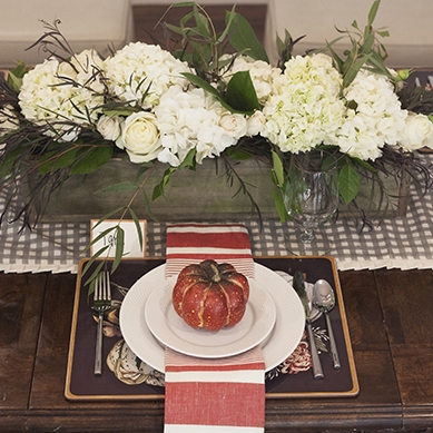 Autumn Orchard - Tablescape Includes:Checkered Table Runner, Cork Place Mat, Plate, Napkin, Napkin Ring, and Place Card$14.99 per tablescapeYour guests will be whisked away to an autumn orchard with this stunning color palette. Rich warm tones contrast with soft reds, topped off with an adorable pumpkin accessory and coordinating place card.