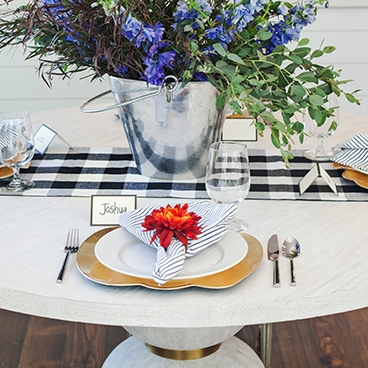 The Golden Pumpkin - Tablescape Includes:Checkered Table Runner, Pumpkin Charger, Plate, Napkin, Napkin Ring, and Place Card$14.99 per tablescapeSimple patterns compliment each other, and are accentuated by a vibrant mum napkin ring. This tablescape brings a unique autumn touch to your dinner party.