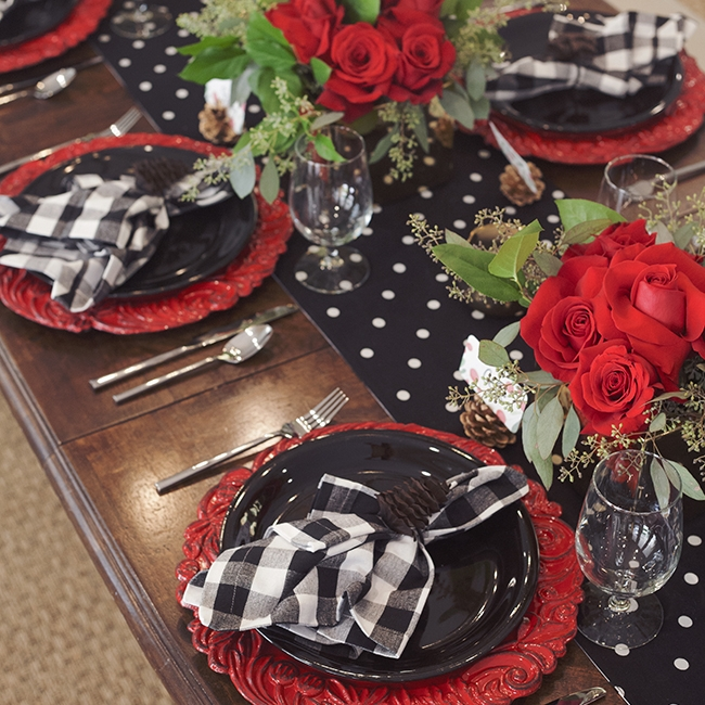 Rejoice With Red - Tablescape Includes:Polka Dot Runner (Black and White Polka Dot Reversible), Charger, Plate, Napkin, Napkin Ring, Place Card Holder/Place Card$14.99 per tablescapeThese soft black and white fabrics are a simple backdrop for the holiday red charger! A gold glitter pine cone adds the perfect finishing touch to this elegant and bright tablescape!