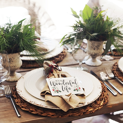 It's a Wonderful Life - Tablescape Includes:Rattan Charger, Rustic Off-White Charger, Plate, Napkin, Napkin Ring, It's A Wonderful Life Accessory$14.99 per tablescapeRattan and rustic off-white chargers, paired with a tan napkin are simple and classic. The table setting is enhanced with a red berry Napkin Ring and finished with an 'It's A Wonderful Life' table accessory to make the table complete!