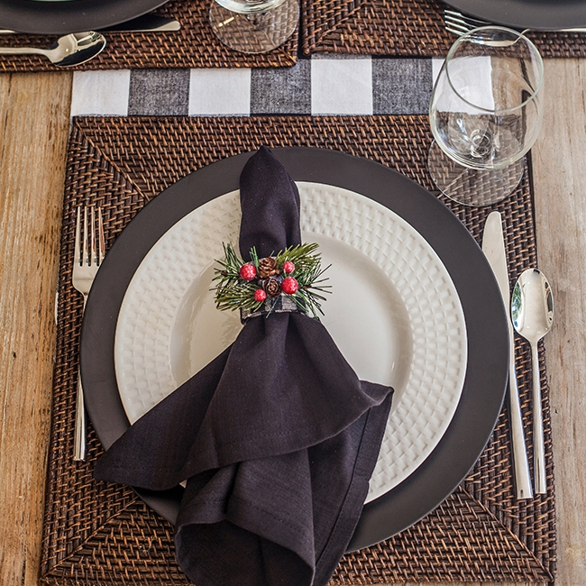 """Plaid Merriment - Tablescape Includes:Checkered Table Runner, Rattan Charger (Large/15"""" Square), Plate, Black Charger, Napkin, Napkin Ring$14.99 per tablescapeThis classic and elegant tablescape begins with a black and white table runner, which is enhanced with a dark rattan place mat. A matte black charger with coordinating napkin and napkin ring are accented with fun frosted berries to add a touch of red to this merry table setting!"""