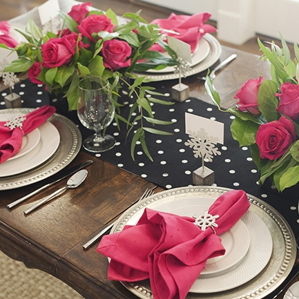 Celebrate With Pink - Tablescape Includes:Polka Dot Runner (Black and White Polka Dot Reversible), Platinum Charger, Plate, Hot Pink Napkin, Napkin Ring, Place Card Holder$14.99 per tablescapeThis stylish winter table setting is a fun way to celebrate this winter. Polka dots, platinum and bright pink are accentuated with silver snowflakes to create a unique holiday tablescape.