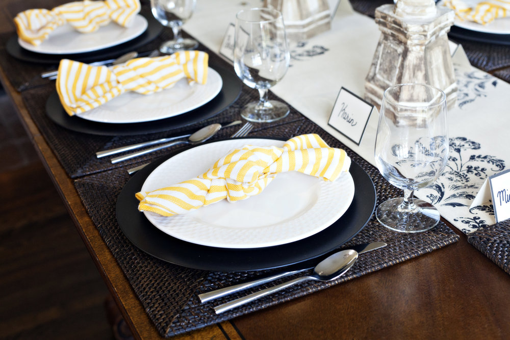 Bee-utiful Affair - Tablescape Includes:Bee embroidered table runner, rattan square place mat, black charger, plate, Yellow striped napkin, Place card$14.99 per tablescapeYour guests will bee happy when gathered around the table! Perfect for any occasion; birthday, anniversary, graduation, retirement; or just because! The yellow splash of color in the napkins make this table setting a delight!