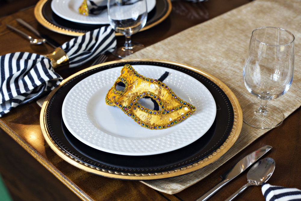 Carnival Soiree' - Tablescape Includes:Gold table runner, gold charger, black bead rimmed charger, plate, black striped napkin, gold napkin ring, gold sequined mask$14.99 per tablescapeDelight your guests with a night of merriment with this sophisticated and fun tablescape! Celebrate Mardi Gras in fashion! Or, Carnival Soiree' is a wonderful addition to any menu, any occasion, and the sequined masks are an added treat for your guests to take home!