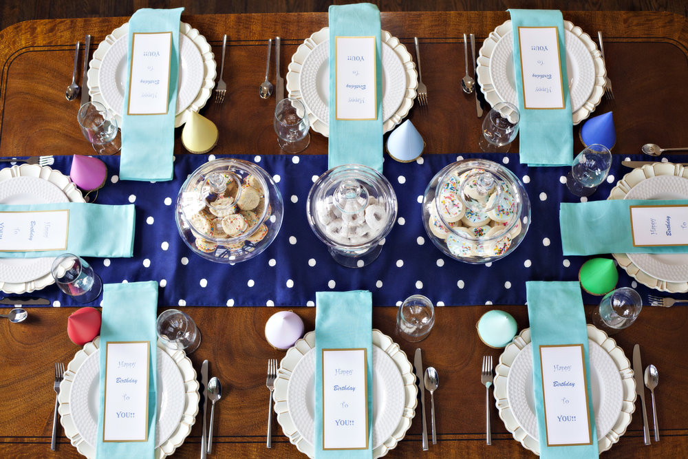 Happy Birthday! - Tablescape Includes:Blue and white polka dot runner, gold rimmed charger, plate, Tiffany blue hued napkin, gold rimmed menu card, gold rimmed party hat$14.99 per tablescapeA whimsical tablescape for adults and children alike! Colorful napkins and a printable card add detail for an occasion to remember. The multi- colored party hats are perfect for all ages, and an added favor to take home!