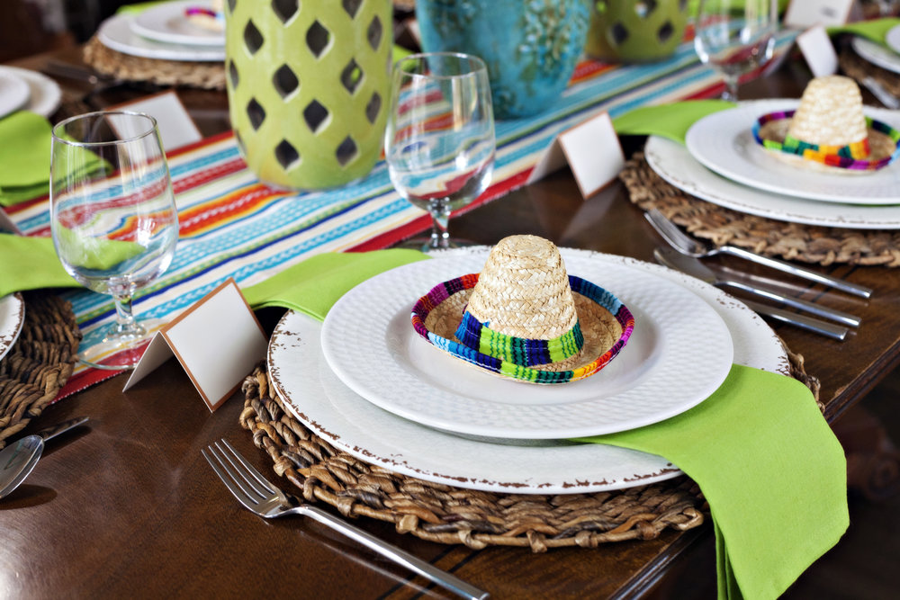 Fiesta! - Tablescape Includes:Striped fringed table runner, rattan place mat, rustic off-white charger, plate, napkin, place card, sombrero table accessory$14.99 per tablescapeEverything needed for a fiesta! A colorful table runner, bright green napkins, and a sombrero table accent set the stage for your next fiesta night. Perfect for a Mexican food themed occasion. Tequila not included!