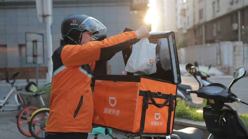 """Deliveryman unpacking someone's """"外卖"""" (delivery) dinner. Photo: 127.net"""