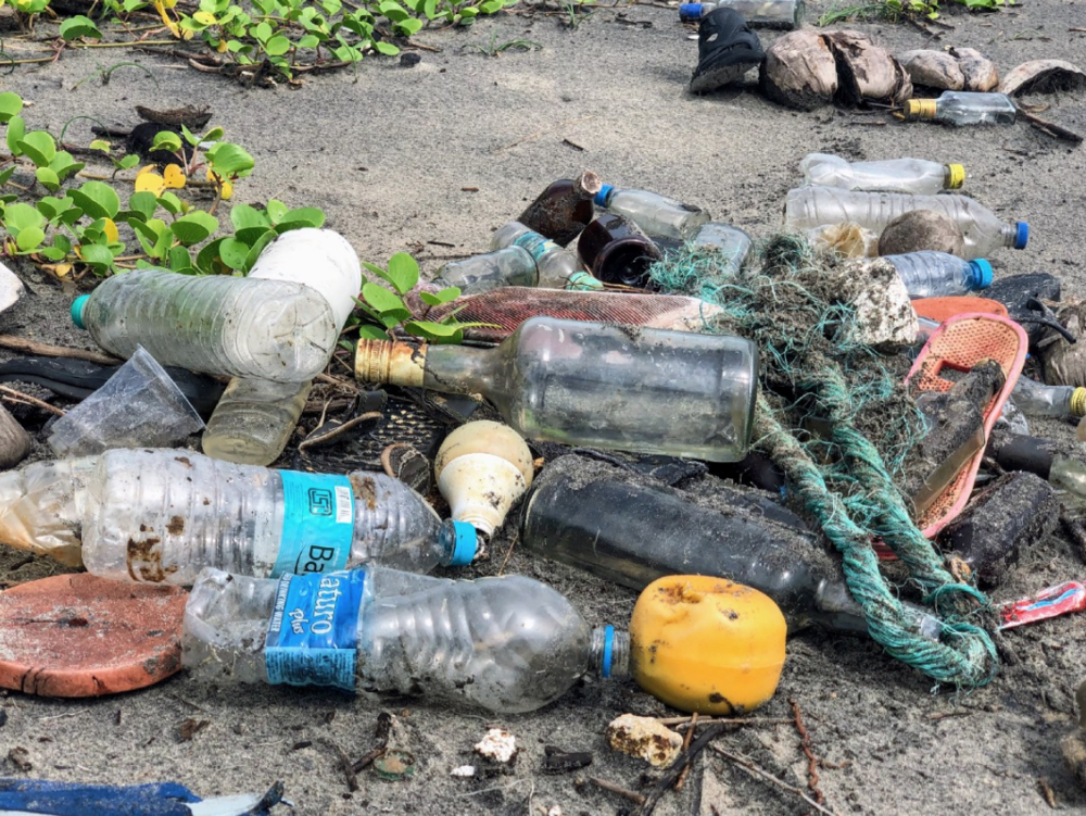 """assorted garbage bottles on sandy surface"" by  John Cameron  on  Unsplash"