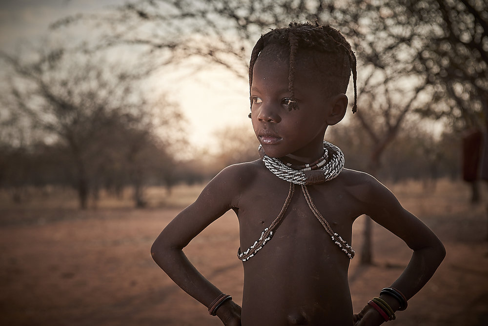 himba teenager, with the decoration denoting he is to be a warrior and protector.  the big necklace is prepared by the women in the family/village, but the smaller ones are usually made by the boy himself.
