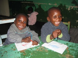 Two boys sitting at a desk with coloring pages in front of them. One boys is smiling into the camera and the other is smiling while looking at something to the right.