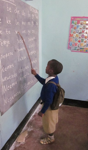 Child with a backpack on at the chalkboard pointing at a lesson written on the board.