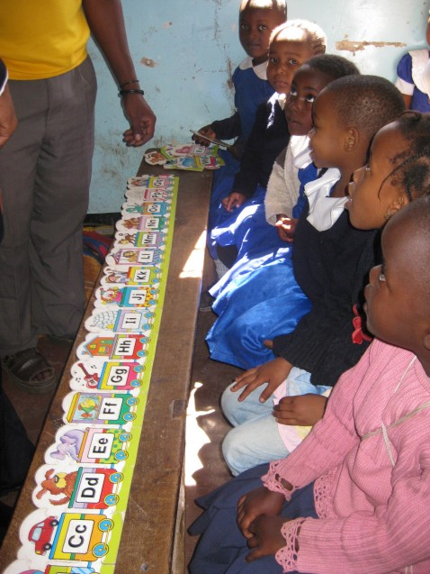 African children sit beside each other with cards of the alphabet in front of them.