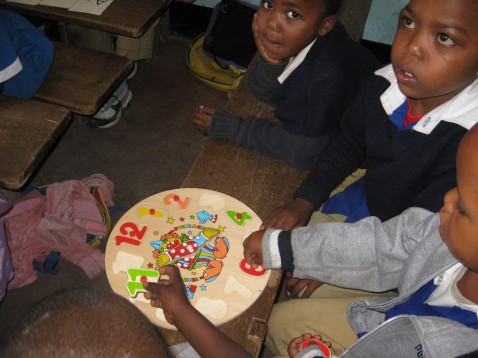African children playing with a numbers puzzle around a table