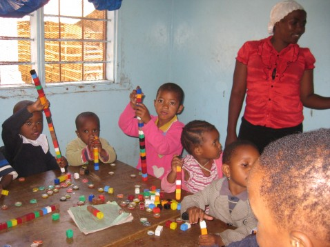 African children in an early childhood classroom setting playing with blocks, a teacher stands beside them.