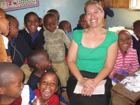 African children and an American woman sit in a classroom in Tanzania smiling at the camera.