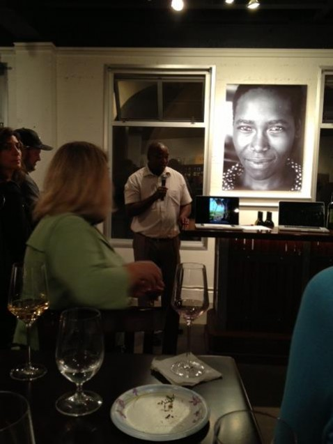 An African man speaking into a microphone, a large photo exhibited beside him and a group of people listening.
