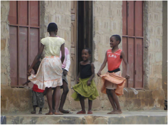 girls dancing outside a building in Tanzania