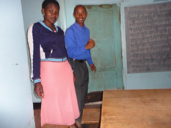 A man and woman stand in a classroom with the chalkboard behind them.