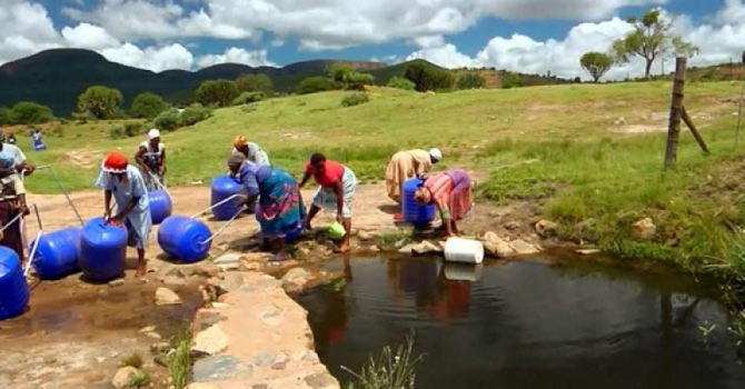 women using the hippo roller at a water source