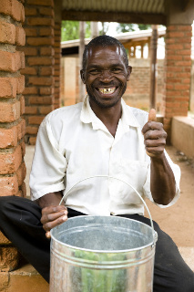 An African man sitting before a metal bucket outdoors