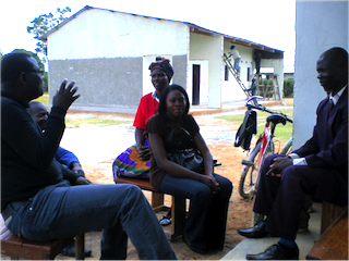Silvia (middle) with colleague Louis Mwewa and others outside a community school in Zambia