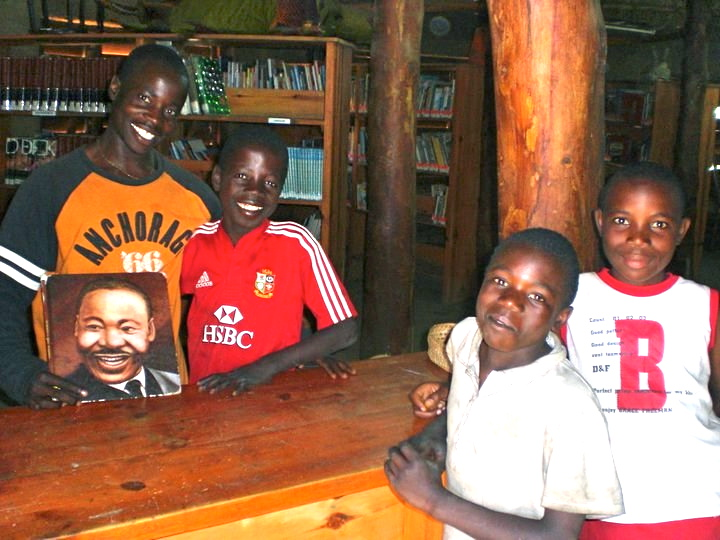 A group of children around a book with Martin Luther King Jr. of the cover