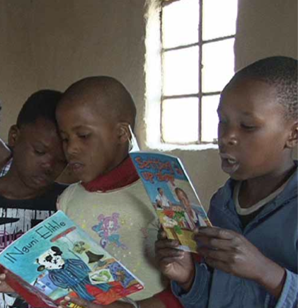 Three African children reading in a school room