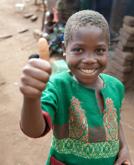 a boy with a thumps up outdoors in Africa