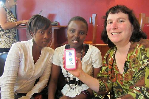 three women in Rwanda, one woman holding a cell phone