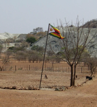 Zimbabwe flag in the ground and waving in the wind along a dirt road