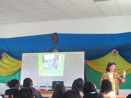 Woman leading a workshop with several students and a screen with an image projected on it.