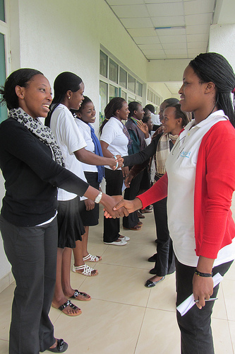 young women shaking hands and talking with eachother