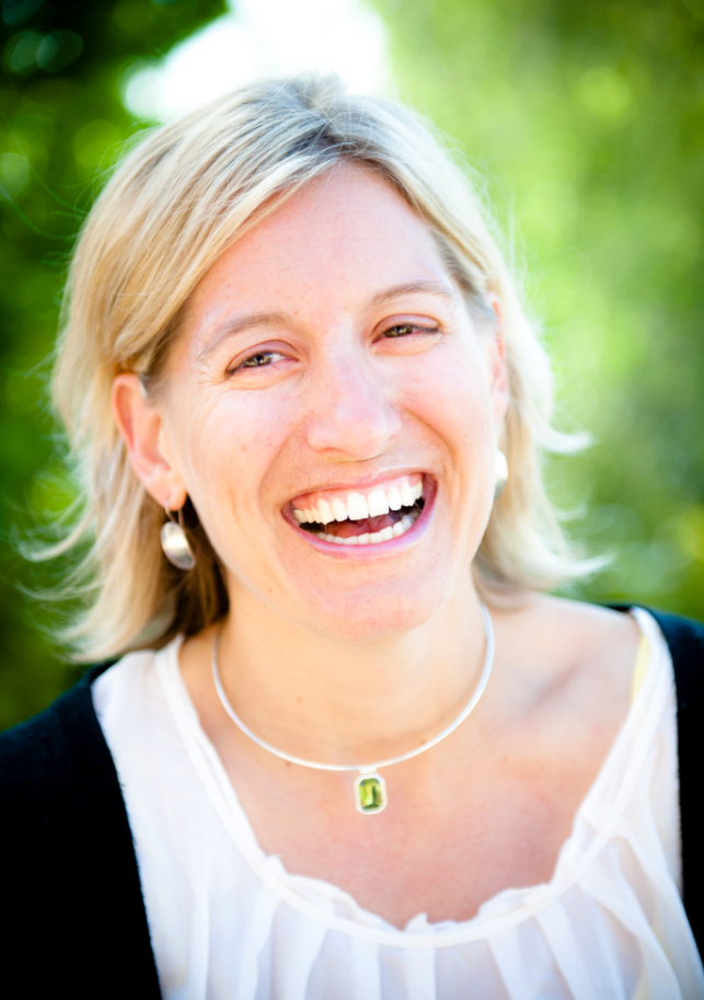 A woman smiling in a sunny outdoor setting with green trees behind her.