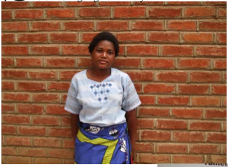 Girl standing before a brick wall wearing a white t-shirt and purple and yellow printed skirt