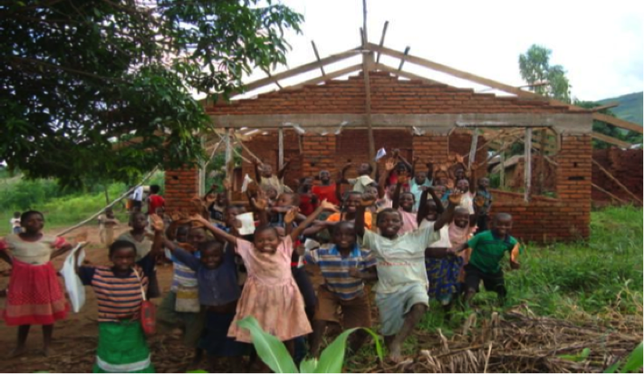 Children smile and hold their arms out outside a school under construction in an African town
